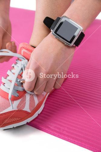 Woman tying her laces of sport shoes