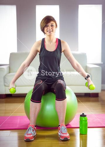 Fit woman lifting dumbbell sitting on ball