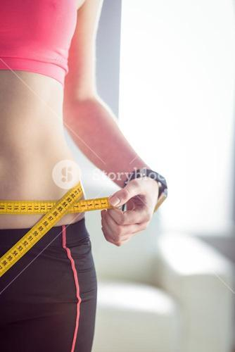 Slim woman measuring waist with tape measure