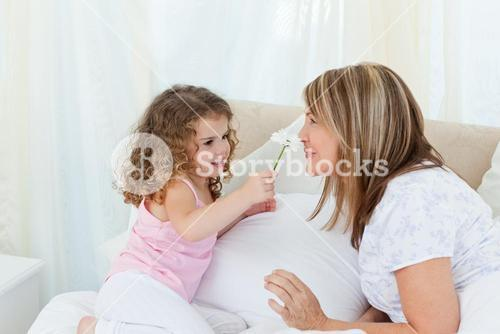 Woman smelling a flower given by her daughter while lying on a bed