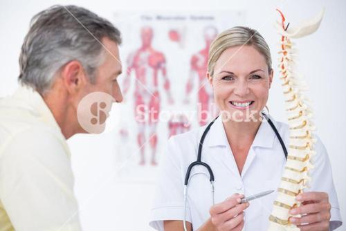 Smiling doctor showing her patient a spine model