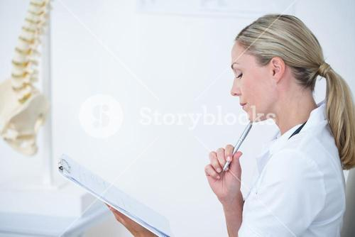Doctor writing on clipboard at her desk