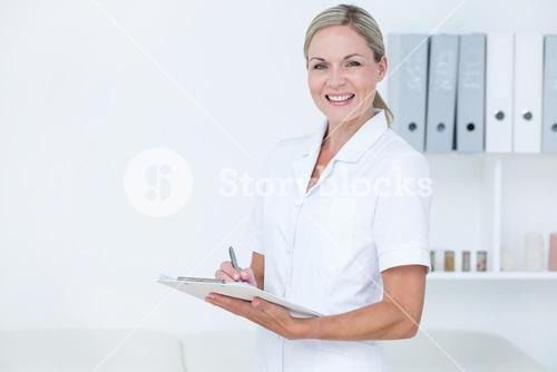 Smiling doctor writing on clipboard