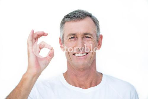 Smiling patient looking at camera and gesturing ok sign