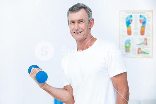 Patient looking at camera and lifting dumbbell