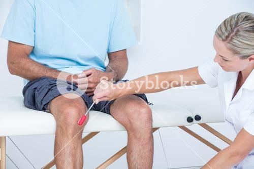 Doctor checking reflexes of the knee of her patient