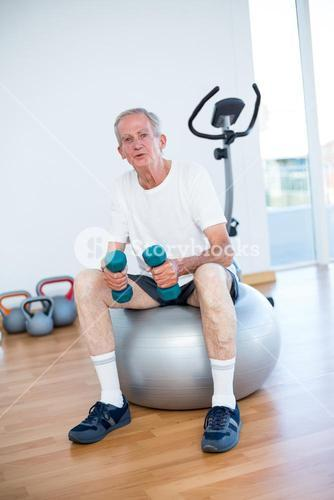 Old man sitting on exercise ball