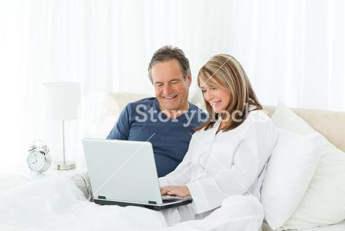 Mature lovers looking at their laptop