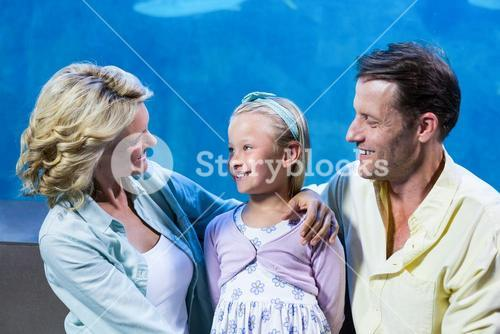 Happy family standing beside the fish tank