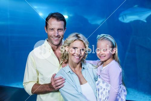 Happy family looking at camera beside the fish tank