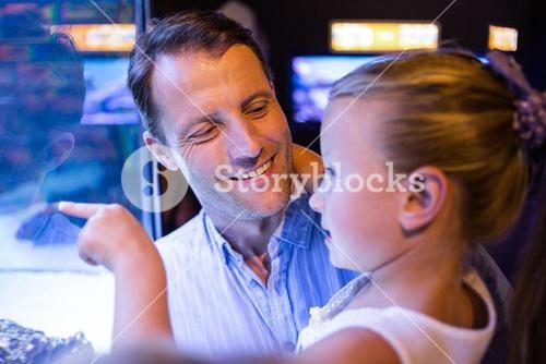 Daughter looking and father looking at fish in tank