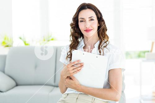 Smiling therapist holding her clipboard