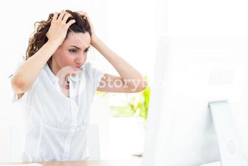 Upset businesswoman sitting at her desk