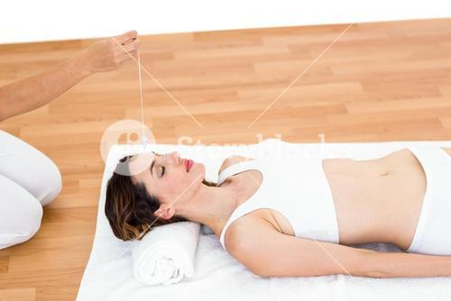 Woman being hypnotized while lying on the floor