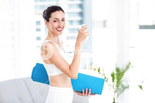 Brunette holding glass of water and exercise mat