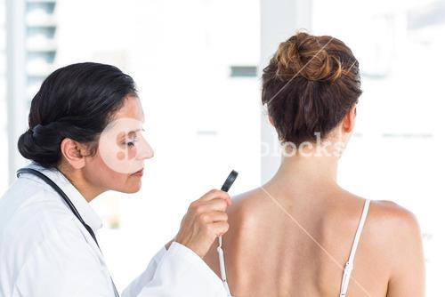 Doctor examining patient with magnifying glass
