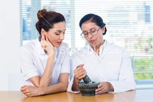 Scientists mixing herbs with pestle and mortar