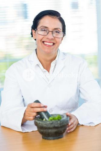 Scientist mixing herbs with pestle and mortar
