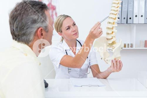 Doctor showing her patient a spine model