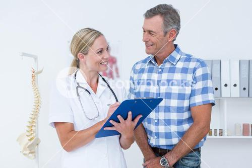 Doctor showing clipboard to her patient
