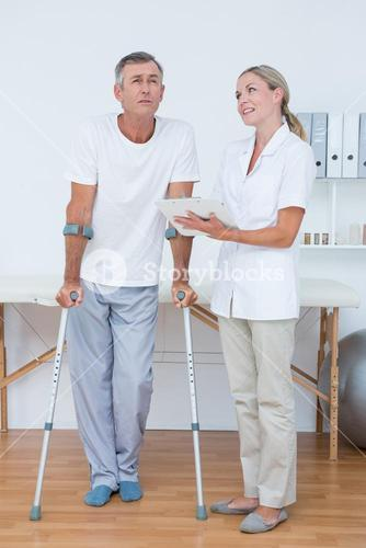 Man with crutch speaking with his doctor