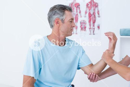 Doctor examining her patient arm