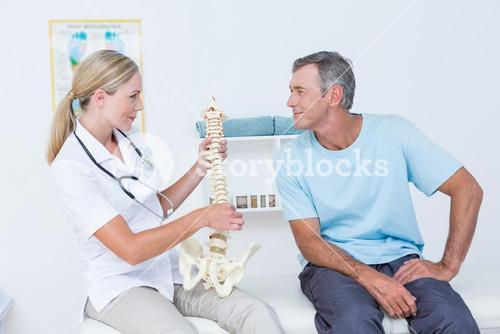 Doctor showing anatomical spine to her patient