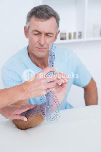 Doctor measuring arm with goniometer