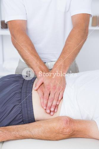 Physiotherapist doing back massage to his patient