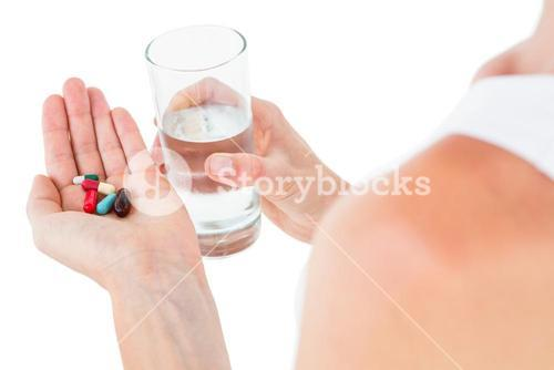 Woman holding batch of pills and glass of water
