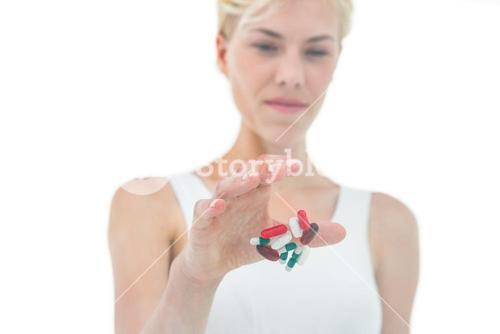 Blonde woman throwing away batch of pills