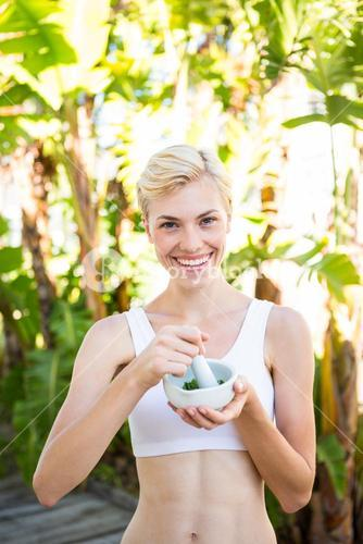 Happy blonde woman mixing herbs