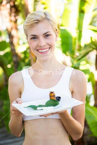Happy blonde woman presenting plate with herbal medicine