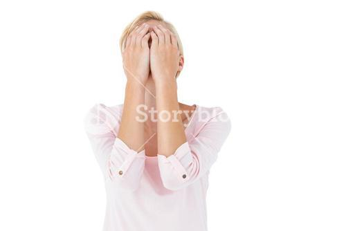 Nervous blonde woman covering her face
