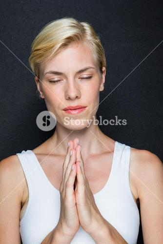 Attractive blonde woman praying
