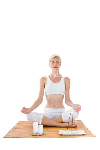 Fit woman meditating on bamboo mat