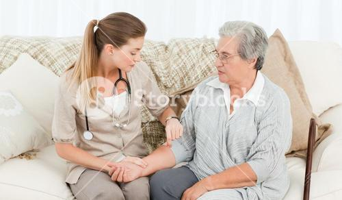 Beautiful nurse taking the pulse of her patient at home
