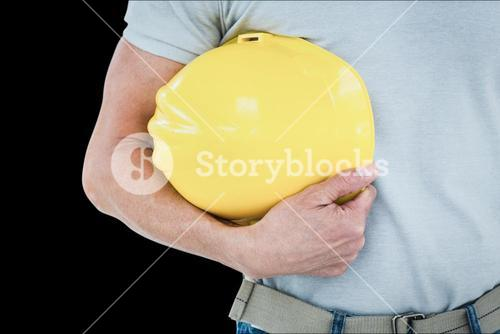 Composite image of technician holding hard hat