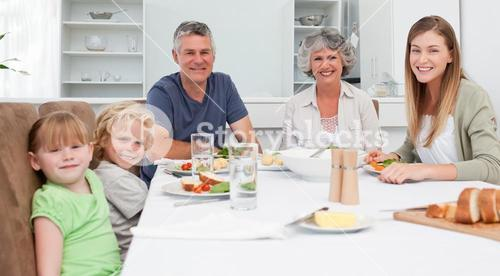 Pretty family looking at the camera while eating their meal