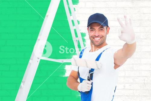 Composite image of happy handyman with paint roller gesturing okay