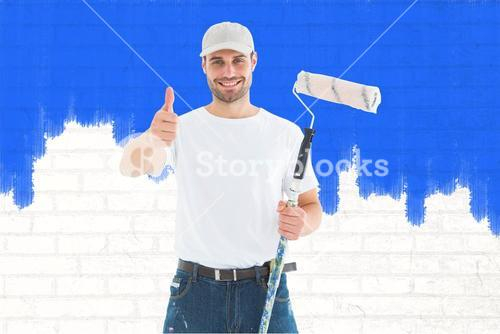 Composite image of happy man with paint roller gesturing thumbs up