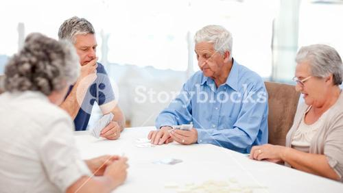 Retired people playing cards together