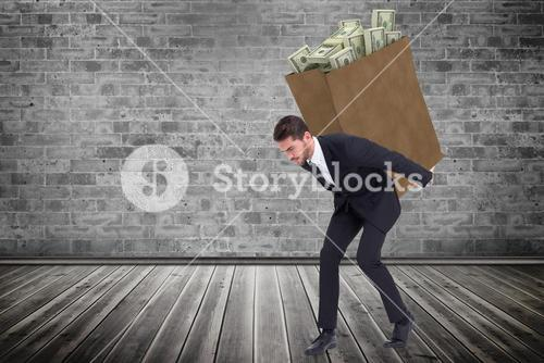 Composite image of businessman carrying something heavy with his back and hands