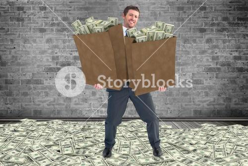 Composite image of businessman carrying bags of dollars