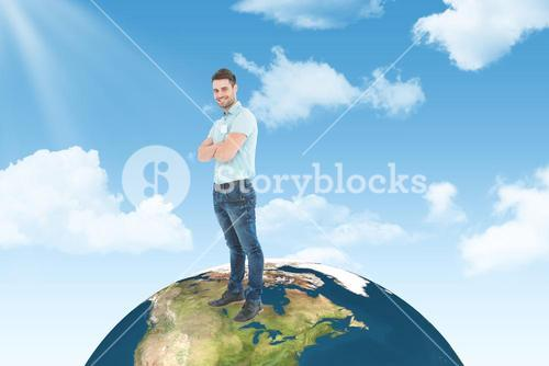 Composite image of smiling young delivery man standing arms crossed