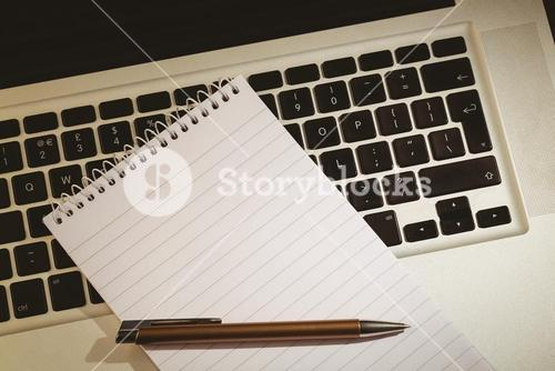 Notepad and pen on laptop