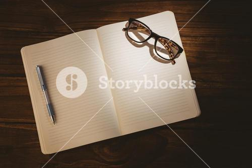 Empty notepad with reading glasses