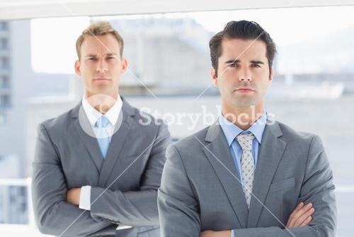 Two businessmen frowning at camera
