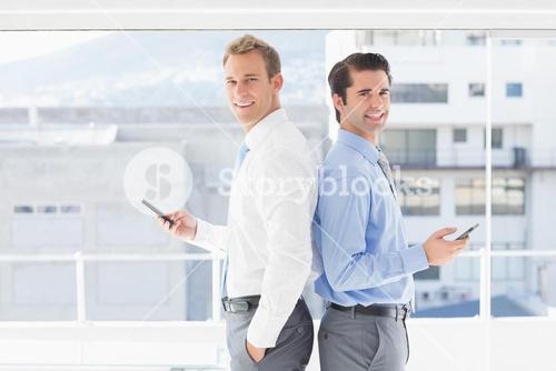 Two businessmen standing back to back