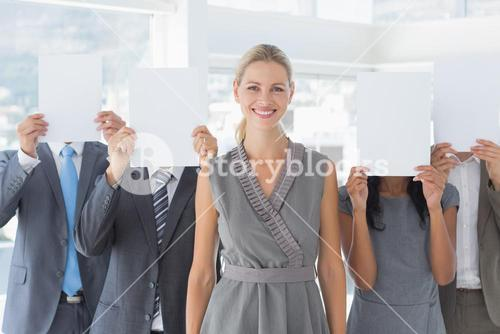 Business colleagues hiding their face with paper